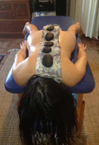 Woman relaxing with hot stones placed on her back